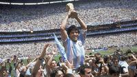 Penyerang Argentina, Diego Maradona, mengangkat trofi Piala Dunia saat usai mengalahkan Jerman Barat pada laga final Piala Dunia 1986 di Meksiko, (29/6/1986). (Photo by - / AFP)