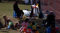 Anggota keluarga berada di taman bermain Institut Pengembangan Sumber Daya Manusia Nasional di Jincheon, Korea Selatan (13/10/2021). Para pengungsi muncul di hadapan publik pada hari Rabu, untuk pertama kalinya sejak mereka tiba pada akhir Agustus. (AFP/Pool/Jeon Heon-kyun)