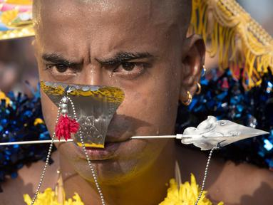 Seorang pria menusuk pipinya dengan batang logam saat Festival Thaipusam di Gua Batu, Kuala Lumpur, Malaysia, Senin (21/1). Prosesi tahunan ini dirayakan oleh umat Hindu di seluruh dunia untuk menghormati Dewa Murugan. (AP Photo/ Vincent Thian)