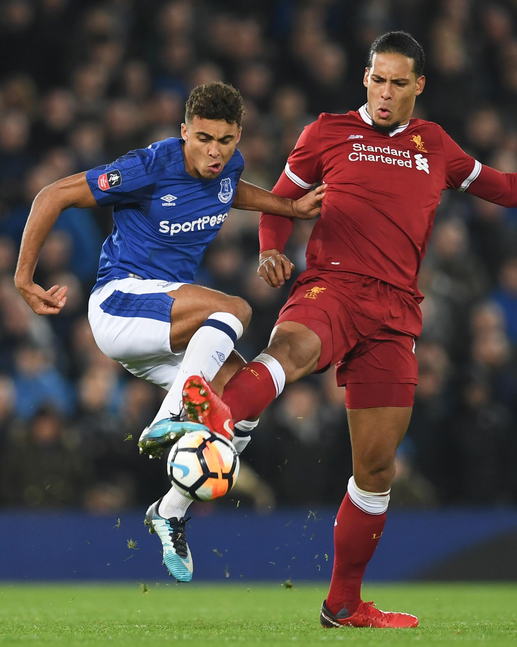 Bek Liverpool, Virgil Van Dijk (kanan) berusaha merebut bola bek Everton, Mason Holgate saat bertanding di Piala FA di Anfield, Inggris (5/1). Liverpool berhak lolos ke babak keempat setelah mengalahkan Everton 2-1. (AFP Photo/Paul Ellis)