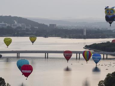 Sejumlah balon udara terbang bebas diatas danau Burley Griffin, Canberra,  Australia, (15/3). Ini dilakukan dilakukan dalam memperingati ulang tahun ke-30 festival Balloon Spectacular Canberra . (REUTERS / Lukas Coch)