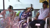 Pasien bernapas dengan bantuan oksigen yang disediakan oleh Gurudwara (Kuil Sikh) di bawah tenda yang dipasang di sepanjang tepi jalan di Ghaziabad, India, Selasa (4/5/2021). Amukan tsunami COVID-19 di India memunculkan kelangkaan oksigen (Money SHARMA/AFP)