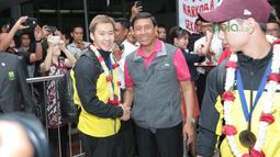 Marcus Gideon bersalaman dengan Ktum PBSI, Wiranto saat tiba di Bandara Soekarno-Hatta, Cengkareng, (20/3/2018). Kevin/Marcus mampu mempertahankan gelar All England 2018. (Bola.com/Nick Hanoatubun)
