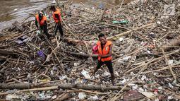 Petugas kebersihan saat mengenakan topeng Spiderman membersihkan sampah yang menumpuk di Pintu Air Manggarai, Jakarta, Senin (12/11). Sampah kiriman berasal dari wilayah Bogor dan Depok. (Liputan6.com/Fery Pradolo)