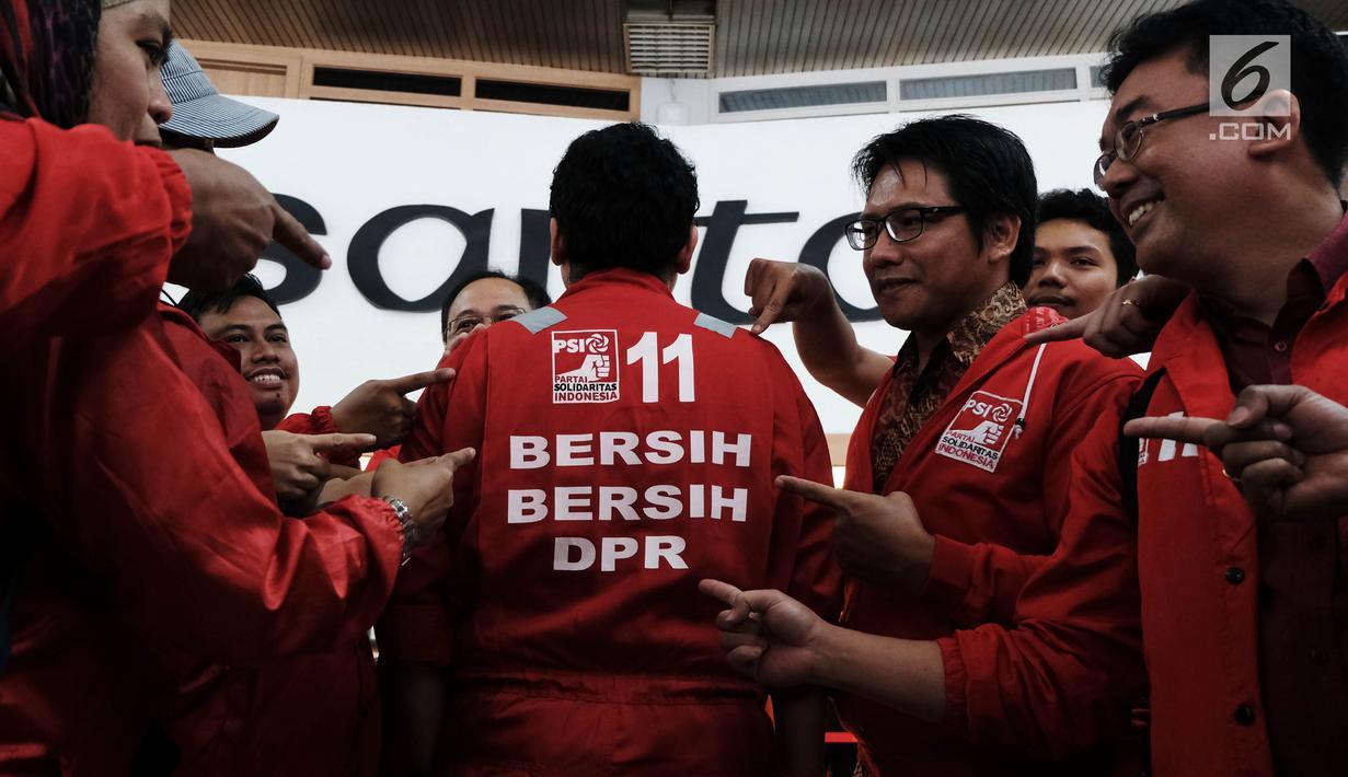 Calon legislatif dari Partai Solidaritas Indonesia (PSI) mendatangi gedung DPR RI di Senayan, Jakarta, Jumat (7/12). Kedatangan mereka untuk kampanye bersih-bersih DPR sambil mengenakan seragam merah ala cleaning service. (Liputan6.com/Johan Tallo)