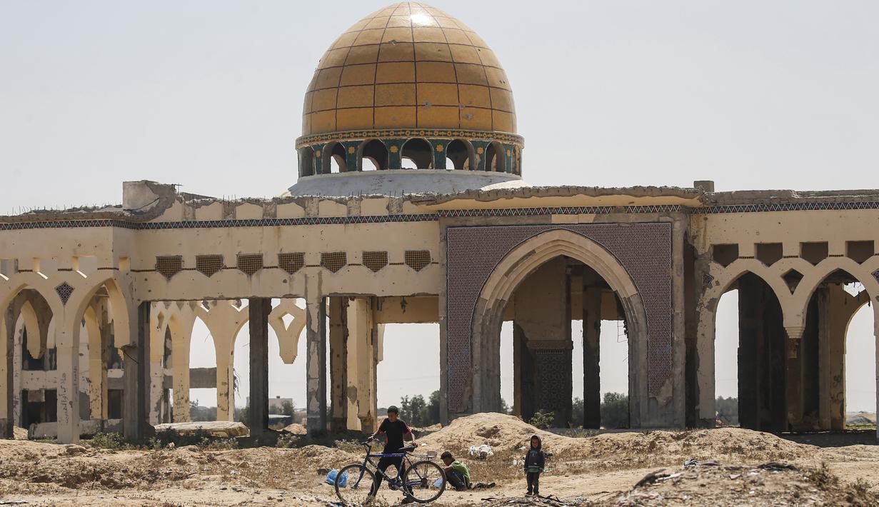"""Anak-anak bermain di depan terminal """"Yasser Arafat International Airport"""" yang hancur dan sepi di Jalur Gaza, di kota Rafah, Palestina (24/6/2019). Bandara ini diresmikan pada November 1998. (AFP Photo/Said Khatib)"""