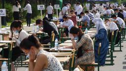 Para siswa Uzbekistan mengikuti ujian masuk luar ruangan, di tengah pandemi COVID-19 yang sedang melanda, di Tashkent pada Rabu (2/9/2020). (Photo by Yuri KORSUNTSEV / AFP)