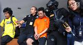 Polisi membawa tersangka pembunuhan satu keluarga di Kota Bekasi saat gelar perkara di Polda Metro Jaya, Jakarta, Jumat (16/11). Tersangka berinisial HS masih memiliki hubungan saudara dengan korban. (Merdeka.com/Imam Buhori)