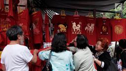 Sejumlah calon pembeli melihat pakaian bertema Imlek yang dijual di kawasan Glodok, Jakarta, Kamis (25/1). Adapun berbagai macam aksesoris yang dijual para pedagang diantaranya lampion, angpao, Sio Anjing, gantungan pintu. (Liputan6.com/JohanTallo)