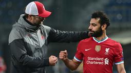 Pelatih Liverpool, Jurgen Klopp, memberikan selamat kepada Mohamed Salah usai timnya meraih kemenangan atas Atalanta pada laga lanjutan Liga Champions 2020/2021 di Gewiss Stadium, Rabu (4/11/2020) dini hari WIB. Liverpool menang 5-0 atas Atalanta. (AFP/Miguel Medina)