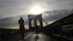 Seorang wanita mengambil foto saat berada di Jembatan Brooklyn, New York City, 3 Desember 2018. Jembatan paling legendaris di kota New York itu memiliki fitur arsitektur yang sangat ikonik dan telah diakui dengan banyaknya penghargaan. (AP/Wong Maye-E)