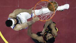 Aksi pemain Warriors, JaVale McGee (kiri) melakukan dunk melewati adangan pemain Cavaliers, Tristan Thompson pada gim ketiga final NBA basketball di Quicken Loans Arena, (6/6/2018). Warriors kalahkan Cavaliers 110-102. (AP/Carlos Osorio, Pool)