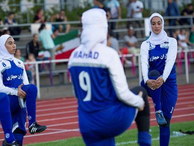 Pesepakbola wanita Iran melakukan pemanasan sebelum pertandingan melawan Jerman di Discover Football tournament di Berlin, Jerman (31/8). Tampil mengunakan hijab pesepakbola wanita Iran jadi pusat perhatian penonton.(REUTERS/Stefanie Loos)