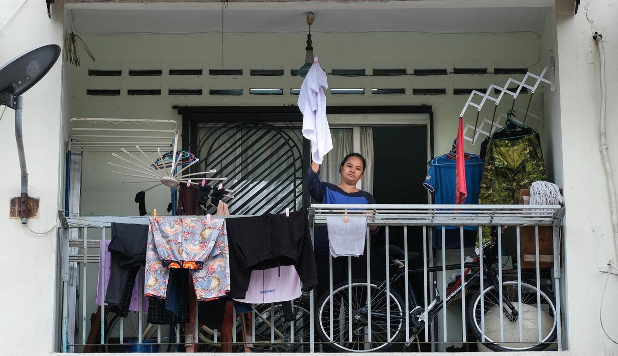 Ibu tunggal Tilda Kalaivani melambaikan kemeja yang digunakan sebagai bendera putih di apartemen sewaannya di Kuala Lumpur pada 6 Juli 2021. Akibat lockdown nasional, banyak keluarga berpenghasilan rendah yang terdampak oleh pandemi COVID-19 semakin kesulitan dalam menjalani hidup. (Mohd RASFAN/AFP)