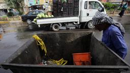 Seorang pekerja melihat tempat sampah yang berisi sisa-sisa pembom bunuh diri yang melakukan pengeboman semalam di Syiah Baghdad di al-Shoala (24/5). (AFP Photo/Ahmad Al-Rubaye)