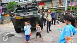 Anak-anak berpose di depan panser Anoa milik TNI di LTC Glodok, Jakarta, Jumat (4/11). Pengamanan tersebut untuk mengantisipasi jika terjadi kerusuhan terkait demo bela islam yang sedang berlangsung. (Liputan6.com/Angga Yuniar)