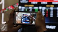 Pengunjung mengabadikan gambar bertuliskan #investor tidak takut di Bursa Efek Indonesia, Jakarta, Senin (18/1). Direktur utama BEI Tito menjelaskan tidak terjadi pengaruh besar pasca teror terhadap perdagangan di BEI. (Liputan6.com/Angga Yuniar)
