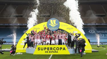 Para pemain Athletic Bilbao mengangkat trofi Piala Super Spanyol usai pertandingan final melawan Barcelona di stadion La Cartuja di Seville, Senin (18/1/2021). Lionel Messi dkk. kalah 2-3 dari Athletic Bilbao pada laga final Piala Super Spanyol. (AFP/RFEF/Pablo Garcia)