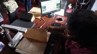 Petugas sedang melakukan digitalisasi naskah kuno dengan memindai untuk dipindahkan ke komputer d Reksa Pustaka.(Liputan6.com/Fajar Abrori)