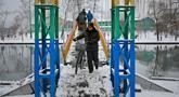Seorang pria menuntun sepedanya saat melintasi jembatan penyeberangan yang melintasi Sungai Pothong di Pyongyang, Korea Utara, Minggu (16/12). Korea Utara saat ini mulai memasuki musim dingin. (AP Photo/Dita Alangkara)