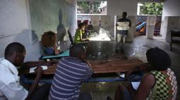 Petugas pemilu menunjukan gambar surat suara saat berlangsungnya pemilu  di Port-au-Prince, Haiti (20/11). Pemilihan umum ini sempat tertunda pada bulan Oktober lalu akibat badai Matthew yang melanda Haiti. (Reuters/Jeanty Junior Augustin)