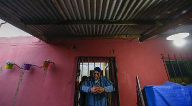 Yamil Peralta berpose dari dalam rumahnya di Jose C. Paz di pinggiran Buenos Aires, Argentina, 29 Juli 2020. Di tengah-tengah lockdown akibat COVID-19, petinju Olimpiade dan profesional ini mendapat pekerjaan di perusahaan sampah untuk memenuhi kebutuhannya. (AP Photo/Marcos Brindicci)