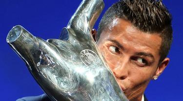 Cristiano Ronaldo mencium trofi Pemain Terbaik Eropa 2016 yang dianugerahkan kepadanya saat acara pengundian grup Liga Champions di Grimaldi, Monako, 25/8/2016).(Reuters/Eric Gaillard)