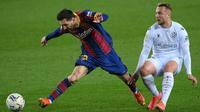 Pemain Barcelona Lionel Messi (kiri) memperebutkan bola dengan pemain Huesca Javier Ontiveros pada pertandingan Liga Spanyol di Stadion Camp Nou, Barcelona, Spanyol, Senin (15/3/2021). Barcelona menang 4-1.  (LLUIS GENE/AFP)