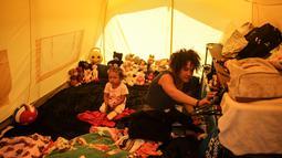 Samir Gonzalez duduk bersama putrinya di dalam tenda mereka di sebuah kamp bagi para migran Venezuela yang tunawisma, di Bogota, Kolombia (21/11). Kamp tersebut dibangun oleh sekretaris kesejahteraan sosial kota. (AP Photo/Ivan Valencia)
