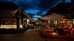 Orang-orang minum di pasar Naschmark yang biasanya penuh sesak di Wina, Austria pada 5 Oktober 2020. Naschmarkt adalah pasar tertua, terbesar, dan terpopuler di Wina kini sepi pengunjung akibat pandemi corona COVID-19. (JOE KLAMAR / AFP)