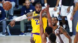 Pebasket Los Angeles Lakers, LeBron James, memberikan umpan kepada rekannya saat melawan Denver Nuggets pada laga NBA di The Arena, Senin (11/8/2020). LA Lakers menang dengan skor 124-121. (AP Photo/Ashley Landis, Pool)