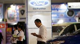 Seorang Salesman saat menunggu pelanggan di pameran mobil di Jakarta Fair, Jakarta, 30 Juni 2015. Pabrikan asal Amerika Tersebut itu tak kuat lagi berkompetisi di Indonesia dan para karyawan akan dirumahkan. (REUTERS / Nyimas Laula)