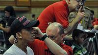 Relawan Starkey Hearing Foundation memakaikan alat bantu dengar pada seorang penyandang tunarungu di Gedung Kemensos, Jakarta, Jumat (27/3/2015). Alat ini diberikan gratis Kemensos bekerjasama dengan Starkey Hearing Foundation (Liputan6.com/Faizal Fanani)