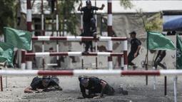 Dua kadet Palestina melewati rintangan kawat berduri saat berlatih fisik dengan militer Hamas, Brigade Ezzedin al-Qassam, di Kota Gaza (20/7/2019). Sejumlah pemuda Palestina direkrut Hamas untuk menjadi bagian anggotanya. (AFP Photo/Mahmud Hams)