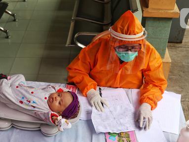 Bidan mengenakan alat pelindung diri (APD) saat melakukan imunisasi kepada bayi di Puskesmas Karawaci Baru, Tangerang, Banten, Rabu (13/5/2020). Pelayanan imunisai sesuai jadwal ini diberikan kepada bayi untuk menambah kekebalan imun tubuh. (Liputan6.com/Angga Yuniar)