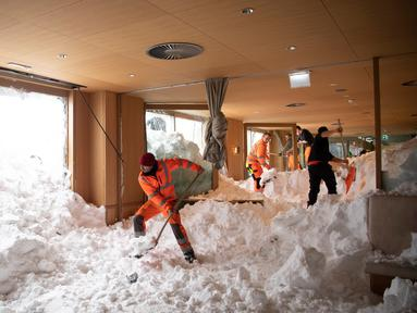 Petugas membersihkan longsoran salju yang masuk ke dalam Hotel Saentis di Schwaegalp, Swiss, Jumat (11/1). Longsoran salju nyaris mengubur Hotel Saentis. (Gian Ehrenzeller/Keystone via AP)
