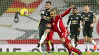Gelandang Manchester United, Bruno Fernandes, berebut bola dengan pemain Liverpool, Thiago, pada laga Liga Inggris di Stadion Anfield, Minggu (17/1/2021). Kedua tim bermain imbang 0-0. (Michael Regan/Pool via AP)