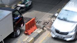 Kedaraan melintasi penutup selokan yang ambles di kolong Manggarai, Jakarta, Kamis (14/3). Penutup selokan tersebut kembali ambles meski sudah diperbaiki berkali-kali. (merdeka.com/Iqbal Nugroho)