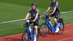 Bek Jerman Marcel Halstenberg (kiri) dan Mats Hummels (kanan) tiba dengan sepeda untuk sesi latihan latihan menjelang UEFA EURO 2020 di World of Sports Campus di Herzogenaurac (11/6/2021). Jerman berada di grup F Euro 2020 bersama Portugal, Prancis dan Hungaria. (AFP/Christof Stache)