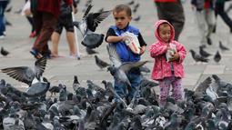 Anak-anak memberi makan kawanan merpati di Alun-Alun Bolivar, Bogota, 2 Oktober 2018. Pemerintah Bogota berusaha mengurangi jumlah populasi merpati melalui larangan bagi pengunjung untuk tidak memberi makan lagi burung-burung itu. (AP/Fernando Vergara)
