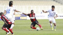 Pemain Persipura Jayapura, Ricky Kayame (tengah) melepaskan tendangan saat melawan Arema FC dalam laga pekan ke-5 BRI Liga 1 2021/2022 di Stadion Madya, Jakarta, Rabu, (29/9/2021). Persipura kalah 0-1. (Bola.com/ M Iqbal Ichsan)