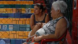 Orang-orang bersantai di anak tangga yang terkenal dengan nama Selaron Steps atau Escadaria Selarón di Rio de Janeiro, Brasil pada 9 Desember 2019. Di setiap anak tangga ada ubin keramik dengan warna yang berbeda-beda  yang berasal dari 60 negara di dunia. (Photo by David GANNON / AFP)