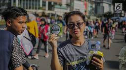 Warga menunjukkan stiker ajakan menggunakan hak pilih pada kegiatan sosialisasi pemilu di kawasan Bundaran HI, Jakarta, Minggu (14/4). Sejumlah Komunitas mensosialisasikan kegiatan pemilu damai tanpa hoaks dan golput menjelang pelaksanaan pemilu 17 April 2019 mendatang. (Liputan6.com/Faizal Fanani)