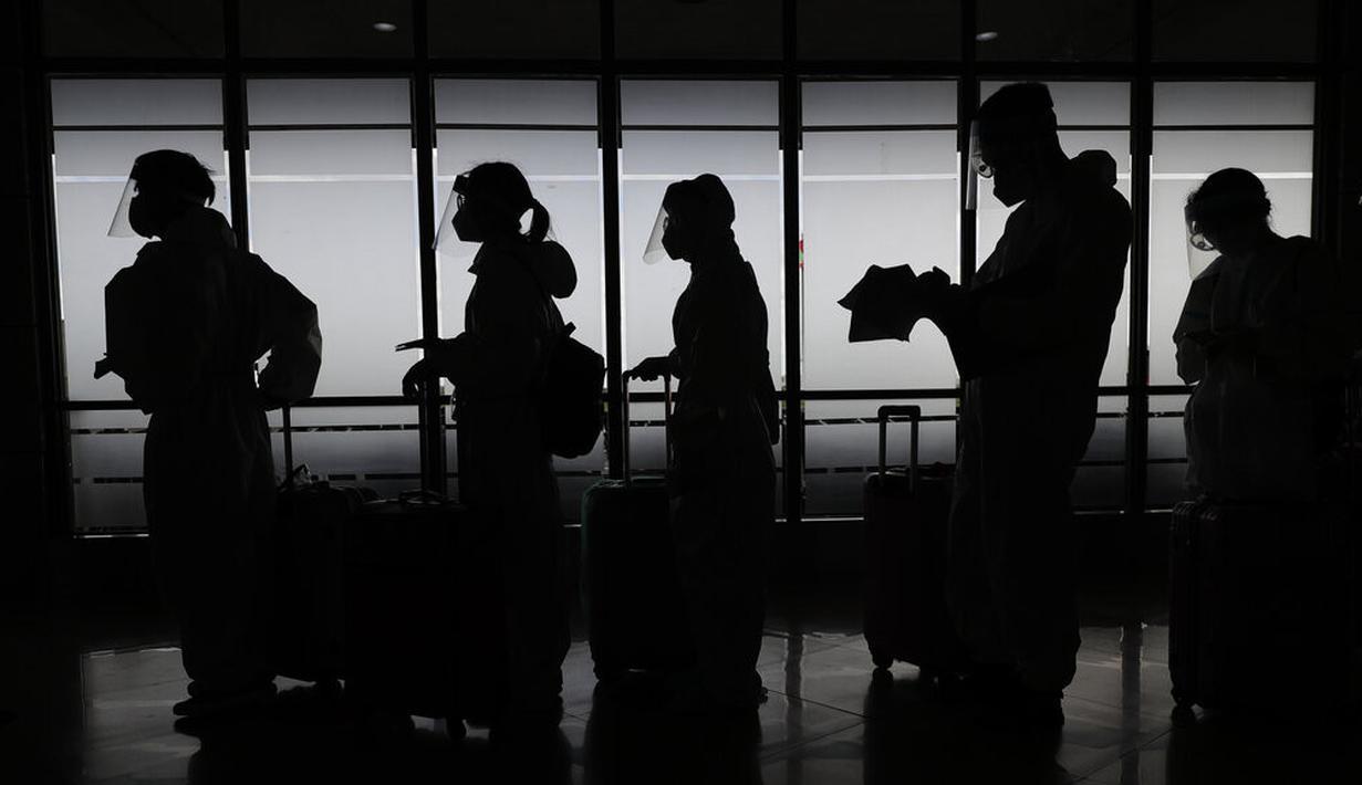 Penumpang asing yang mengenakan pakaian pelindung bersiap untuk penerbangan mereka ke China di Bandara Internasional Manila, Filipina, Senin (18/1/2021). Infeksi virus corona COVID-19 di Filipina telah melonjak melewati 500 ribu kasus.  (AP Photo/Aaron Favila)