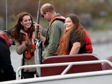 Ekspresi Kate Middleton saat sang suami, Pangeran William berhasil menangkap ikan berukuran besar pada saat memancing bersama di Haida Gwaii, Kanada, (30/9). (REUTERS/Chris Wattie)