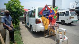 Abdul Karim (65) sopir angkotan Jurusan Ciputat-Muncul menunggu pembeli saat menjual layangan hias di Pingir Jalan Siliwangi, Tangerang Selatan, Banten, Senin (29/9/2020). Abdul Karim beralih profesi menjual layangan hias akibat penumpang sepi untuk memenuhi kebutuhan dapur.  (merdeka.com/Dwi Narwok