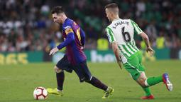 Striker Barcelona, Lionel Messi, berusaha melewati pemain Real Betis, Canales, pada laga La Liga 2019 di Stadion Benito Villamarin, Minggu (17/3). Barcelona menang 4-1 atas Real Betis. (AP/Miguel Morenatti)