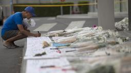 Seorang pria menulis pesan untuk korban penembakan massal di mal Terminal 21 Korat di Nakhon Ratchasima, Thailand, Senin, (10/2/2020). Pelaku penembakan massal, Jakraphanth Thomma berhasil ditembak mati oleh petugas. (AP Photo/Sakchai Lalit)