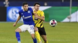 Gelandang Schalke, Amine Harit (kiri) berebut bola dengan bek Borussia Dortmund, Mateu Morey dalam laga lanjutan Liga Jerman 2020/21 pekan ke-22 di Veltins Arena, Sabtu (20/2/2021). Schalke kalah 0-4 dari Borussia Dortmund. (AP/Martin Meissner/Pool)