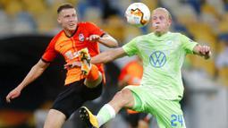 Pemain FC Shakhtar Donetsk, Mykola Matviyenko, berebut bola dengan pemain VfL Wolfsburg, Xaver Schlager, pada laga Liga Europa di Stadion NSK Olimpiyskiy, Kiev, Rabu (5/8/2020). Shakhtar Donetsk menang 3-0 atas Wolfsburg. (AP/Efrem Lukatsky)